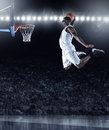 Basketball Player scoring an athletic, amazing slam dunk Royalty Free Stock Photo