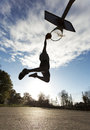 Basketball player slam dunk silhouette of a in the air about to on a sunny day Royalty Free Stock Photos