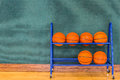 Basketballs in a storage rack blue metal along green wall on wooden gym floor copy space Royalty Free Stock Image