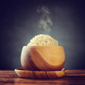 Basmati brown rice cooked organic in wooden bowl with hot steam smoke on dining table low light setting with retro revival style Stock Photo