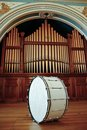 Bass drum large sitting on stage in front of pipe organ Stock Image