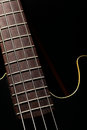 Bass fret board vertical detail of the of a guitar on a dark background Stock Images
