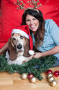 Basset hound wears santa hat at christmas a forlorn looking wearing a comedy shares a moment with his owner an attractive female Royalty Free Stock Photos