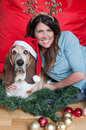 Basset hound wears santa hat at christmas a forlorn looking wearing a comedy shares a moment with his owner an attractive female Royalty Free Stock Image