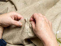 Basting closeup of senior woman s hands linen border with needle and thread Royalty Free Stock Images