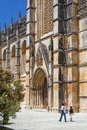 Batalha monastery portugal july locals passing by the south portal of the masterpiece of the gothic and manueline unesco Royalty Free Stock Photo