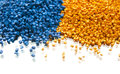 Batch of plastic polymer granules blue and yellow Stock Photo