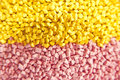 Batch of plastic polymer granules yellow and pink Royalty Free Stock Photo