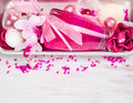 Bath cosmetic set with pink perfume bottle aroma salt ribbon and bath flowers spa background copy space Royalty Free Stock Photos