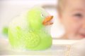 Bath duck and bathing child in the background Royalty Free Stock Photo