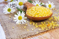 Bath salt on wooden spoon with chamomile on mat Royalty Free Stock Photo