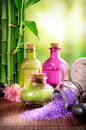 Bath salts and body oil on wood mat vertical composition nature bamboo bokeh background Royalty Free Stock Image