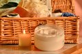 Bath time basket wicker full of flannels and sponges with cream and candle Stock Image