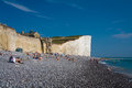 Bathers at seven sisters cliffs on a beach Stock Photo