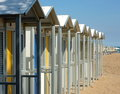Bathing boxes on a beach colourful in rows with some umbrellas Royalty Free Stock Images