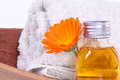 Bathing oil calendula blossom with flask and towel Stock Photo