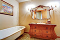 Bathroom with claw foot tub and antique vanity carved wood cabinet mirror Stock Photos