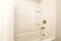Bathroom interior. View of white bath tub and white shower curtain.