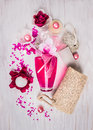 Bathroom set with glass pink bottle sponge scrub oil balls sea salt and bath flowers on white wooden background top view Royalty Free Stock Image