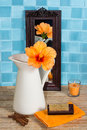Bathroom still life with hibiscus flower in a jug beautiful exotic orange reflected small mirror leaning against turquoise Stock Photo
