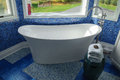 Bathtub in a blue tiled modern bathroom Royalty Free Stock Images
