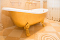 Bathtub old fashioned luxirious golden bath tub in a bathroom Stock Photography