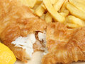 Battered fish and chips deep fried cod takeaway meal with lemon Royalty Free Stock Photos