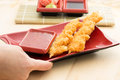 Battered shrimp on red dish with thai and soy sauce ginger and wasabi on bamboo mat Stock Images