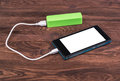 Battery power bank charging smartphone on wooden background Stock Images