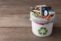 Battery recycle bin with old element on wood table. Royalty Free Stock Photo