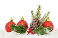 Baubles and foliage on snow red christmas seasonal against a white background Royalty Free Stock Photos