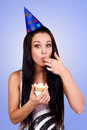 Bautiful caucasian girl blowing candles on her cake blue back Royalty Free Stock Images