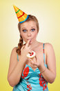 Bautiful caucasian girl blowing candles on her cake yellow background Stock Photo