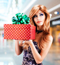 Bautiful woman holds the birthday gift red box with green ribbon indoors adult girl thinking about present Stock Photo