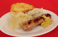 Bavarian bratwurst dinner on white plate with sauerkraut and potatoes against red background and red napkin Royalty Free Stock Image