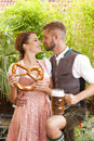 Bavarian couple in traditional costume with beer and brezel Royalty Free Stock Photo