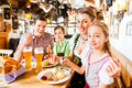 Bavarian family in german restaurant eating having traditional meal Stock Photography