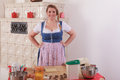 Bavarian girl in dirndl in front of a table with ingredients for baking.