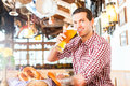 Bavarian man drinking wheat beer wearing traditional dress in german restaurant Royalty Free Stock Photo