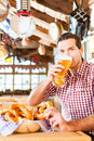 Bavarian man drinking wheat beer wearing traditional dress in german restaurant Royalty Free Stock Image