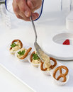 Bavarian pretzels with topping cooks human hand is preparing cream dip image taken on a food trade fair for specialists Stock Image