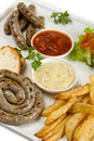Bavarian sausages on the grill french fries and salad Royalty Free Stock Photo