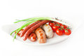 Bavarian sausages with vegetables on a white plate Stock Image