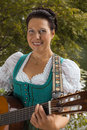 Bavarian woman in dirndl smiling while playing guitar at the lake middle aged and braided her hair stands on and Royalty Free Stock Image