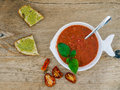 A bawl of tomato soup on a wooden desk background Stock Images