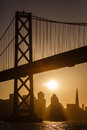 Bay bridge tower and san francisco skyline at sunset silhouettes buildings as sailboat glides under Royalty Free Stock Images