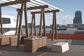 Bbq area in docklands public wooden at victoria harbor promenade with boats southern star waterfront city and light clouds on Stock Images