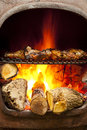 Bbq flame grilled oven chicken being cooked in a wood burning chiminea Stock Images