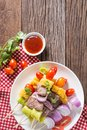 Bbq meat on sticks, kebab skewers with vegetable sticks and tomato sauce on wooden background. Royalty Free Stock Photo