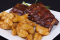 Bbq ribs close up with potato wedges on a white plate Royalty Free Stock Image